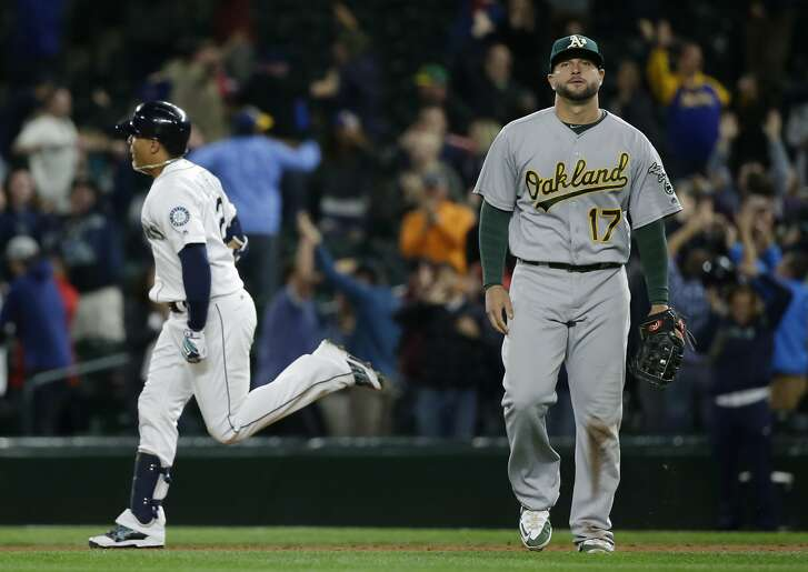 Seattle Mariners' Leonys Martin, left, rounds the bases past Oakland Athletics first baseman Yonder Alonso after hitting a two-run walk-off home run in the ninth inning of a baseball game, Tuesday, May 24, 2016, in Seattle. The Mariners won 6-5. (AP Photo/Ted S. Warren)