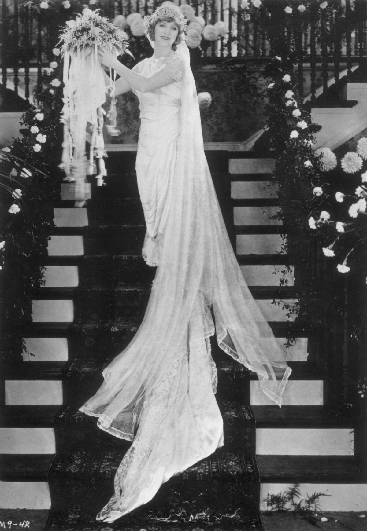 American film actress Mary Pickford (1893 - 1979), radiant in a wedding dress circa 1920.