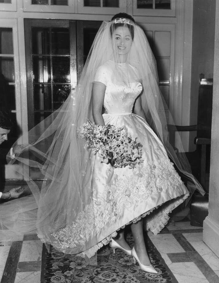13th December 1960:  Actress and author Jackie Collins celebrates her marriage to businessman Austin Wallace at Grosvenor House in London after a registry office ceremony. Her white satin wedding dress with intricate beading cost $400. Photo: Getty Images