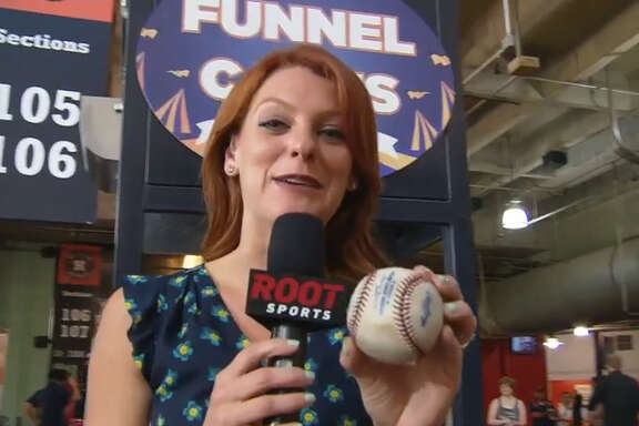 Root Sports reporter Julia Morales shows the ball that the Astros' George Springer hit into a funnel cake deep fryer on Tuesday night at Minute Maid Park.