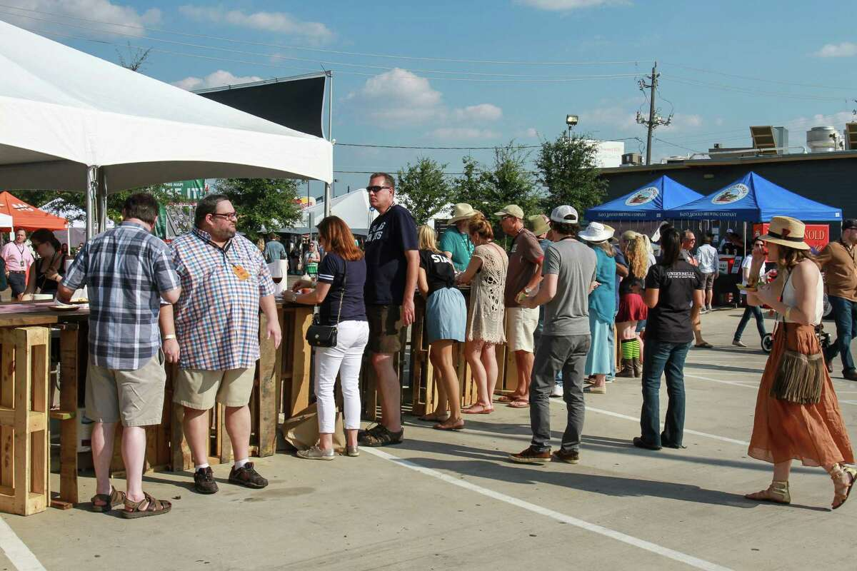 People standing at a table eating barbecue at 2015 Southern Smoke, a huge barbecue event sponsored by Underbelly.