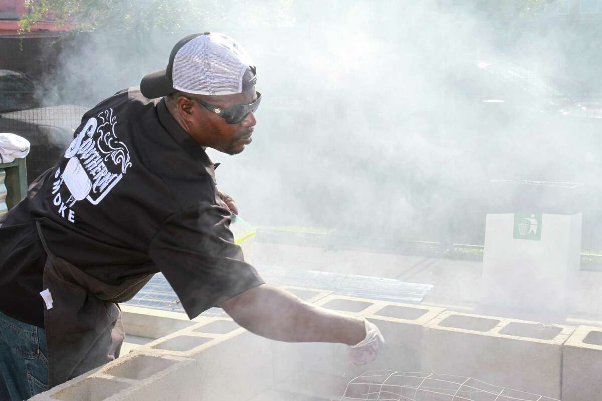 Rodney Scott seasoning a whole hog at 2015 Southern Smoke, a huge barbecue event sponsored by Underbelly.
