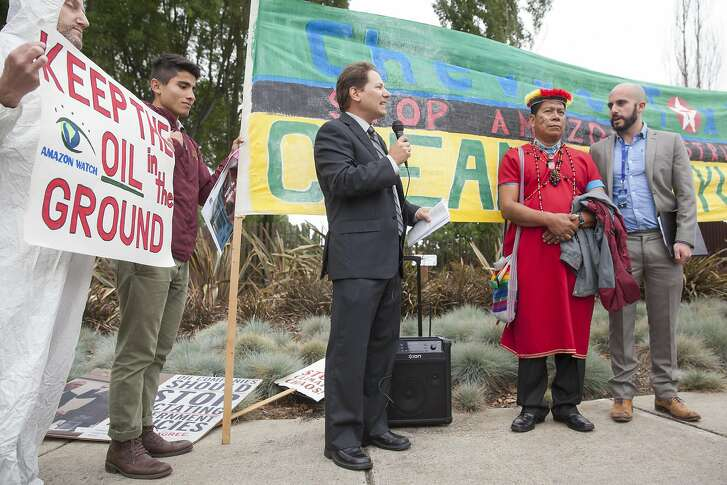 Paul Paz y Mino, Associate Director of Amzon Watch  (center) briefs protestors on the presentation to Chevron CEO John Watson with Secoya indigenous leader Humberto Piaguaje  (right center) of Ecuador after attending the annual Chevron shareholders meeting outs side the Chevon headquarters in San Ramon, California, USA 25 May 2016. (Peter DaSilva/Special to The Chronicle)