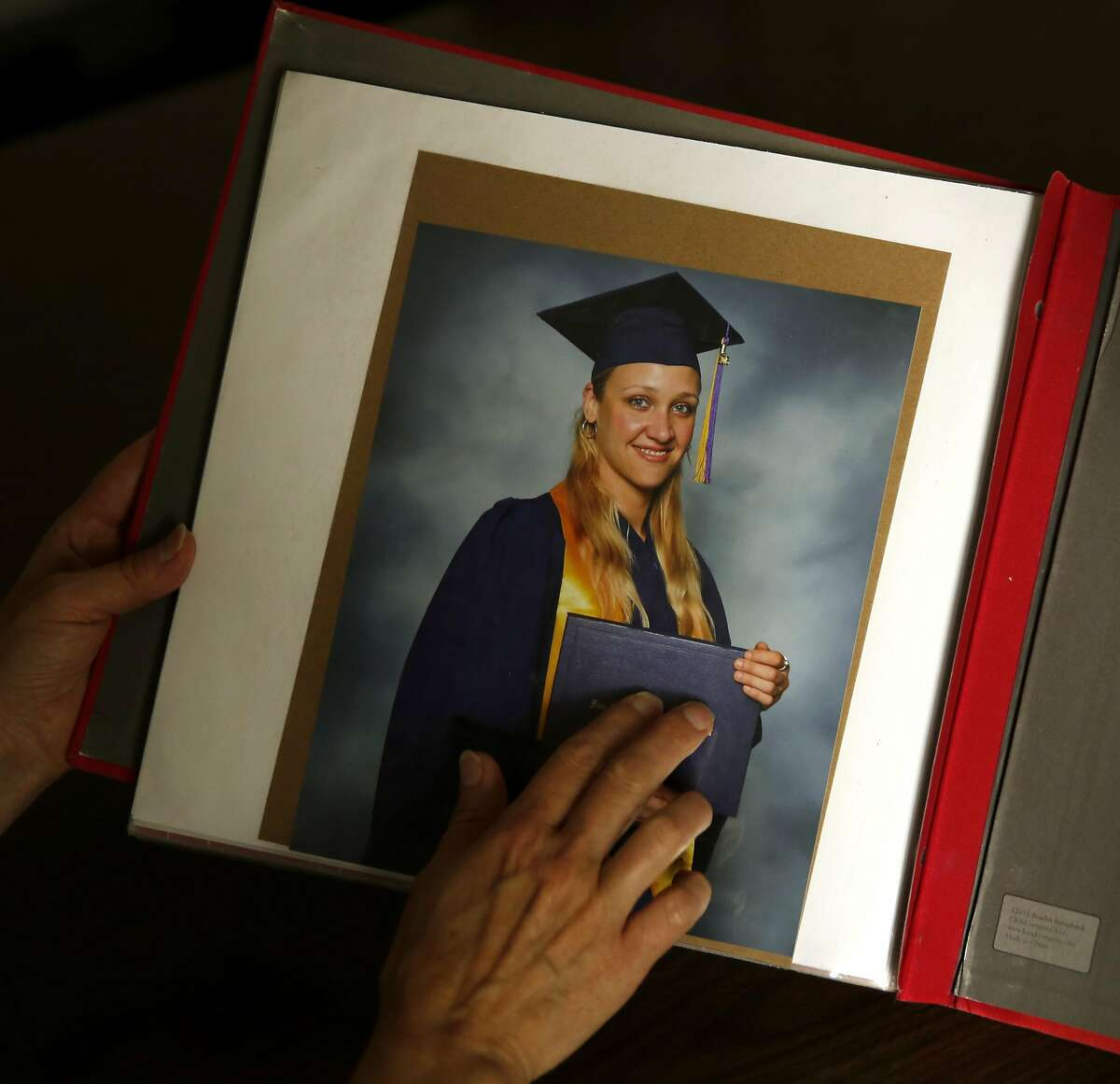 Esther Raiger touches a graduation photograph of Jillian Sobol on the last page of Sobol's scrapbook detailing her adoption story.