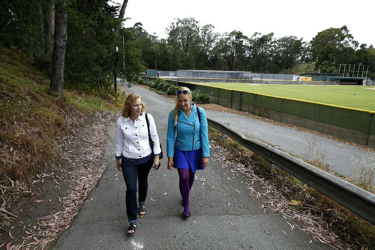 Esther Raiger (left) and Jillian Sobol walk away from the former site of the dormitory where Raiger helped Sobol as a newborn in a cardboard box on the San Francisco State University campus in 1984.
