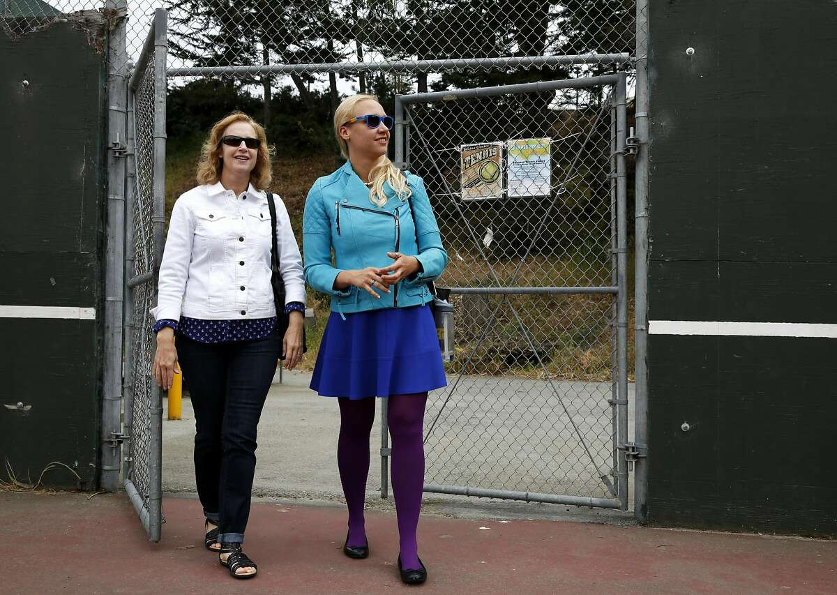 Esther Raiger (left) and Jillian Sobol walk onto tennis courts that replaced the dormitory where Raiger helped Sobol as a baby on the San Francisco State University campus.