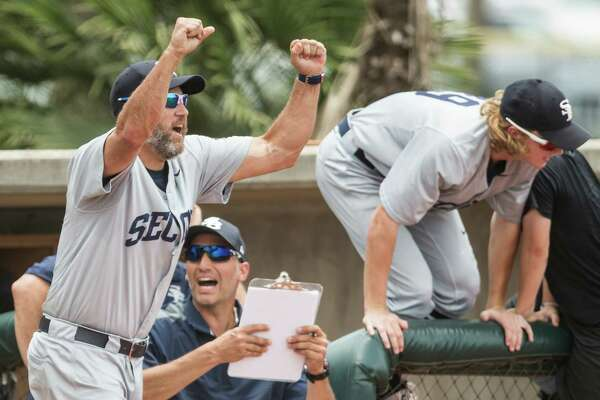 Second Baptist head coach Lance Berkman, left, and assistant Andy Pettitte, seated, celebrate their 7-2 win over Midland Christian for the TAPPS Class 4A state baseball championship at Baseball USA on Wednesday, May 25, 2016, in Houston.