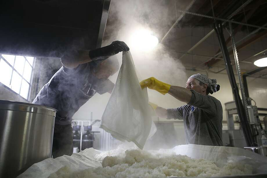 Sequoia Sake partners Warren Pfhal (left) and Jake Myrick (middle) work with rice after cooking on Tuesday, May 24, 2016 in San Francisco, Calif. Photo: Liz Hafalia, The Chronicle