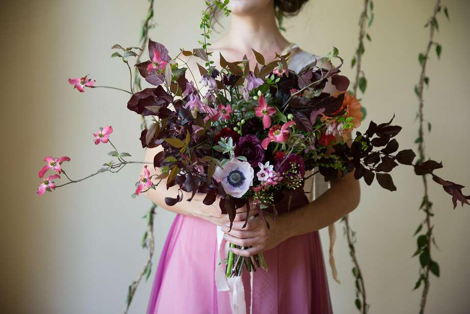"""Betany Coffland blends her two passions, opera and flowers, to create bouquets at Chloris Floral. This bouquet is based on Shoenberg's """"Pierrot Lunaire,"""" a piece about a naive and forlorn puppet, abandoned by his love. The meaning of flowers in this bouquet include mock orange  representing """"deceit,"""" colombine for the namesake of his love, bleeding hearts for """"expressing emotions"""" and anemones for """"forsaken."""" Photo: Paige Green"""