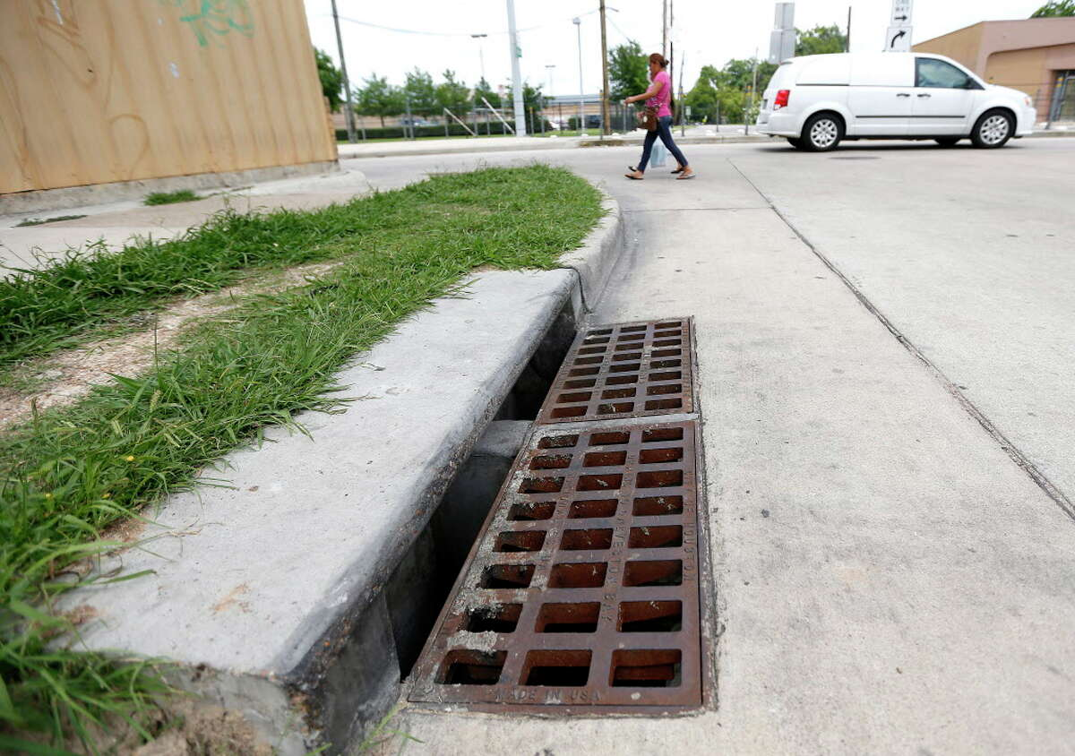 People walk past a storm drain at the corner of North Main and Henry Street, Wednesday, May 25, 2016, where police recovered a knife earlier this morning. Police are investigating to determine if the knife is evidence in the stabbing death of 11-year-old Josué Flores last week.