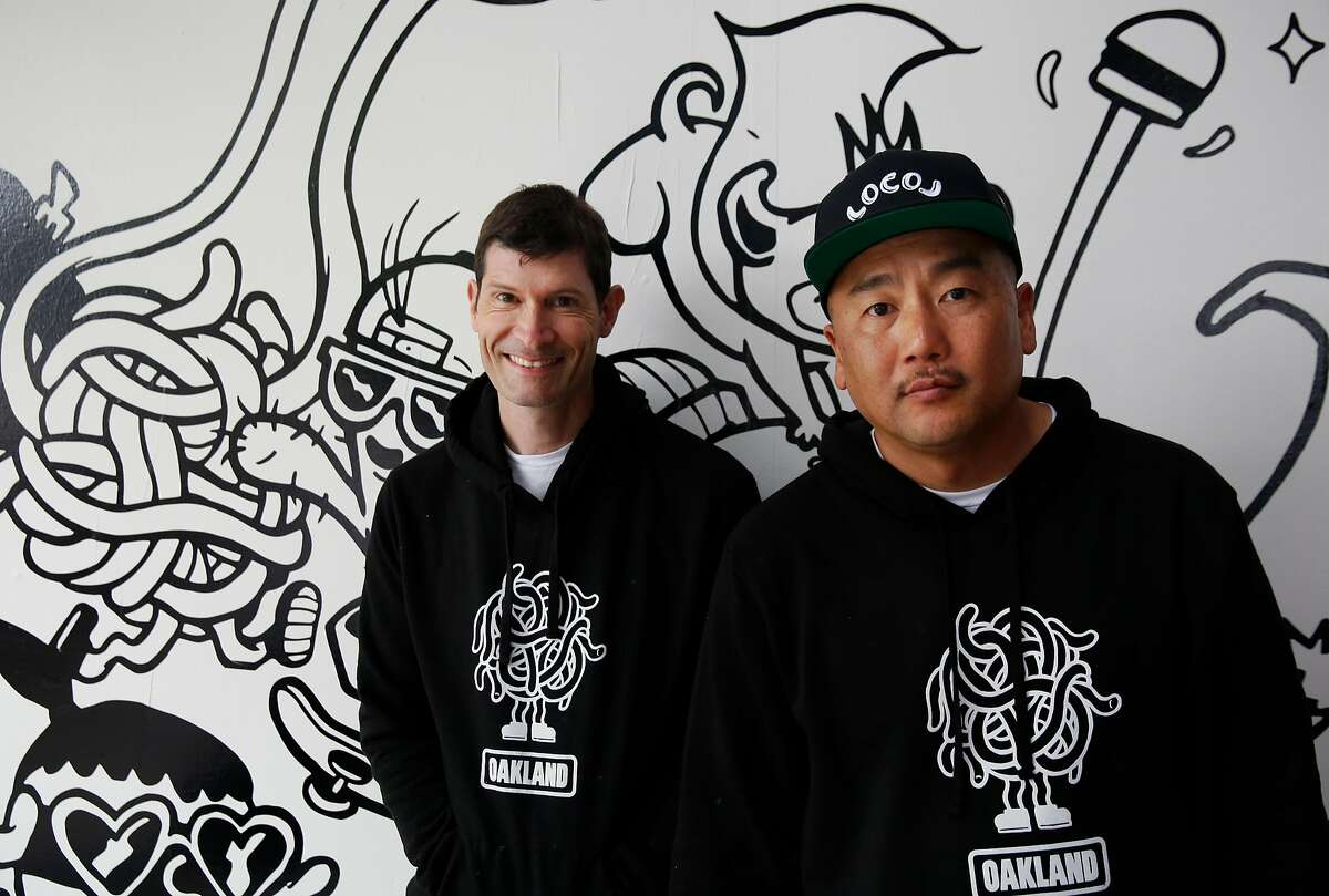Co-founders and Chefs, from left, Daniel Patterson and Roy Choi pose next to artwork on the wall by Bradford Lynn during the opening day of LocoL, which offers affordable and healthy fast food May 25, 2016 in Oakland, Calif. Chefs Roy Choi and Daniel Patterson are co-founders of the restaurant.
