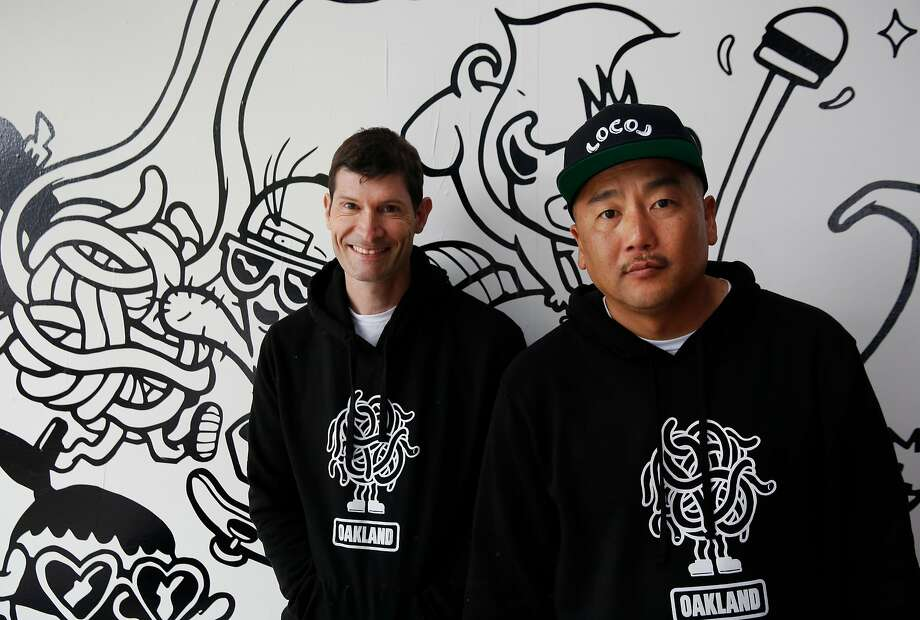 Co-founders Daniel Patterson and Roy Choi pose next to artwork on the wall by Bradford Lynn during the opening day of LocoL, which offers affordable and healthy fast food Photo: Leah Millis, The Chronicle