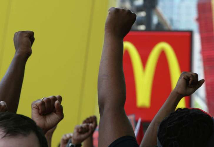 Protesters raise their fist during a rally Wednesday outside a McDonald's in Chicago to demand $15 per hour pay. Demonstrations are also expected Thursday during the shareholders' meeting at McDonald's headquarters in suburban Oak Brook.