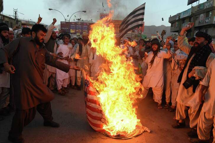 Taliban supporters protesting the drone strike Saturday that killed leader Mullah Akhtar Mansour torch a U.S. flag in the Pakistani city of Quetta on Wednesday.