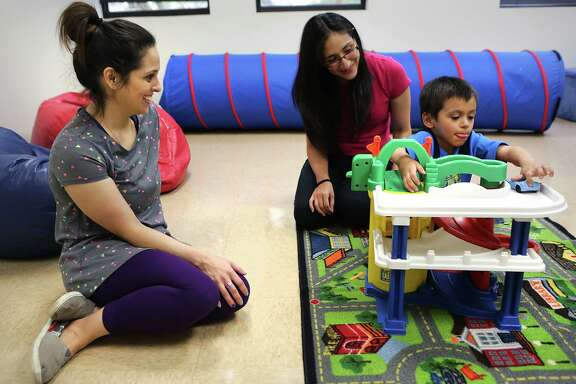 Adriana Sanchez, MA, BCBA, center, works with Gloria Rankin, left, and her son Mason Rankin, 4, on Wednesday, May 25, 2016, in a learning activity room at the Autism Community Network.