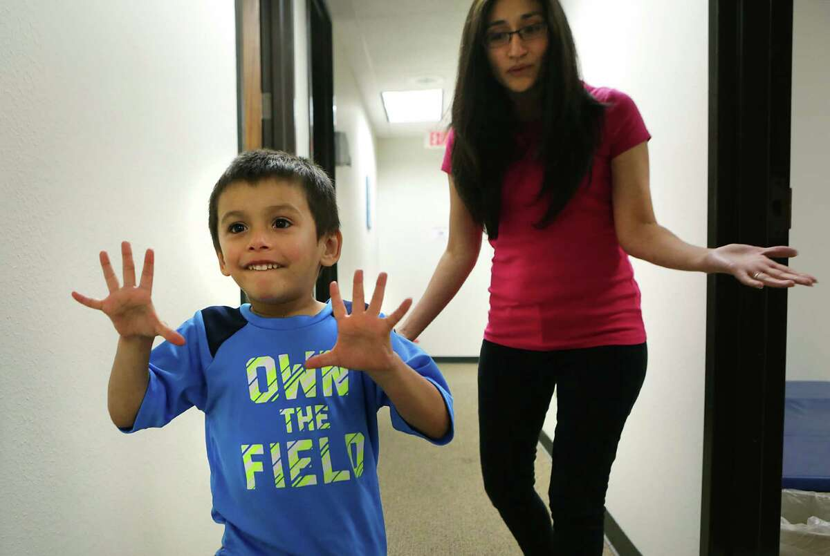 Adriana Sanchez, right, MA, BCBA, takes Mason Rankin, 4, on Wednesday, May 25, 2016, to a learning activity room at the Autism Community Network.