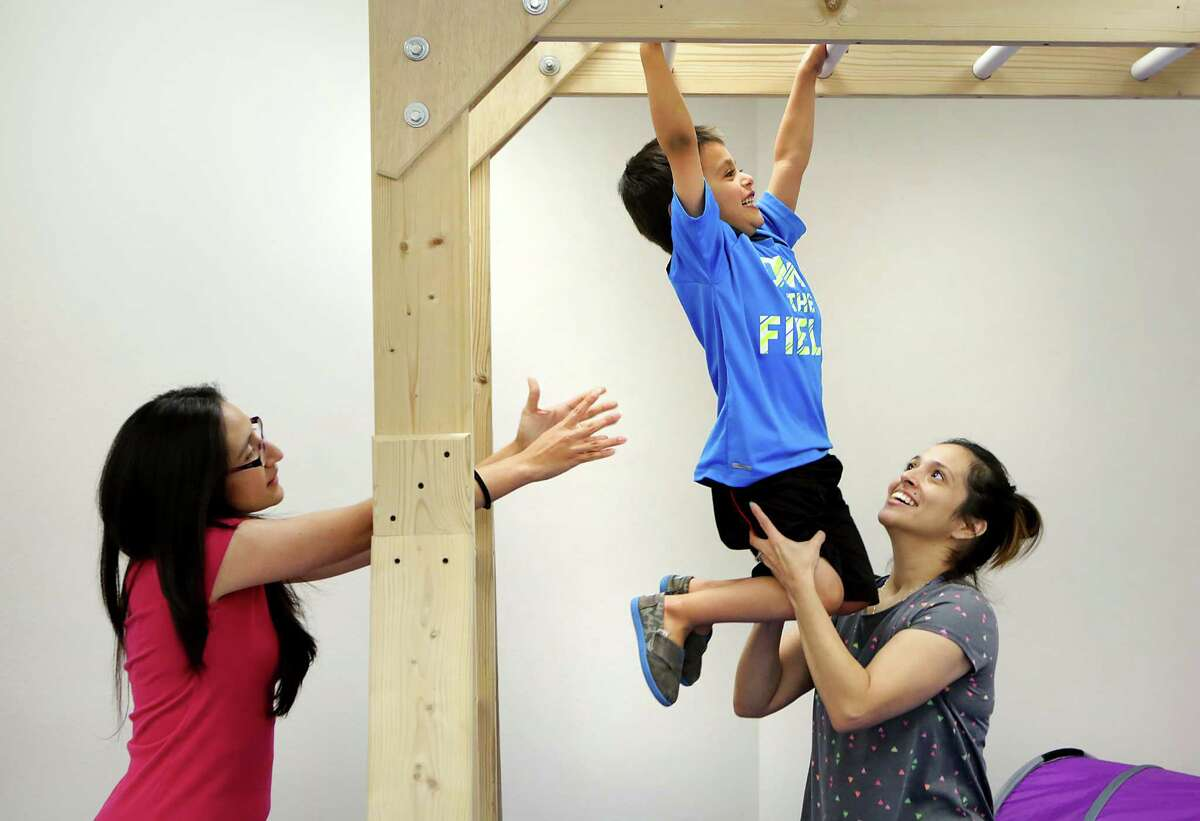 Adriana Sanchez, left, MA, BCBA, works with Gloria Rankin, right, and her son Mason Rankin, 4, on Wednesday, May 25, 2016, in a learning activity room at the Autism Community Network.