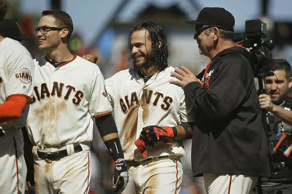 San Francisco Giants manager Bruce Bochy, right, greets Brandon Crawford, center, at the end of their baseball game against the San Diego Padres on Wednesday, May 25, 2016, in San Francisco. San Francisco won the game 4-3 in 10 innings. At left is the Giants' Kelby Tomlinson. (AP Photo/Eric Risberg)
