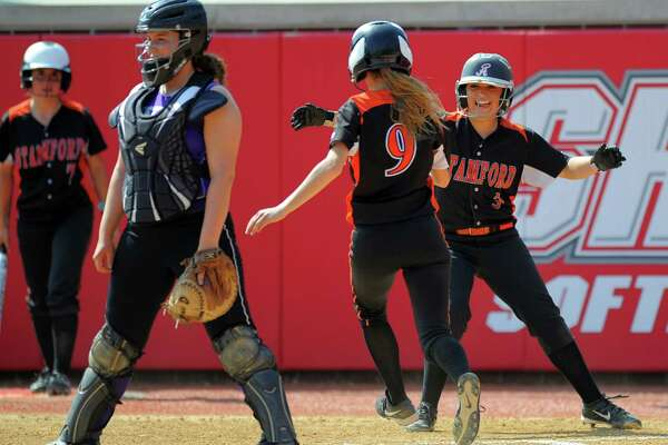 Westhill catcher Jordan Benzaken looks out from home plate as Stamford  Kyra Yacavone and Maddie Santora celebrate scoring off of Kristin Osburn two run RBI single in the third inning against Westhill in a FCIAC Softball Semi Finals at Sacred Heart University in Fairfield, CT on May 25, 2016. Stamford defeated Westhill 6-4.