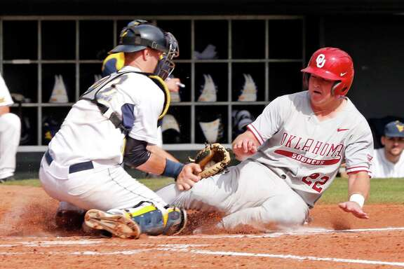 Oklahoma's Sheldon Neuse, right, is tagged out at home by West Virginia's Ray Guerinni in the Big 12 Conference baseball tournament, Wednesday, May 25, 2016 in Oklahoma City, Okla. (Steve Sisney/The Oklahoman via AP)
