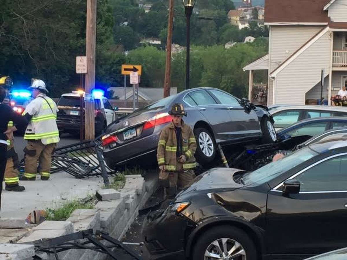 Shelton Police were investigating a crash that occurred on Wednesday, May 25, 2016, involving an eastbound car that witnesses said blew through the stop sign at the corner of Coram Avenue and Wooster Street, then smashed through a wall at the Plumb Library parking lot, injuring at least one person and damaging five other vehicles.