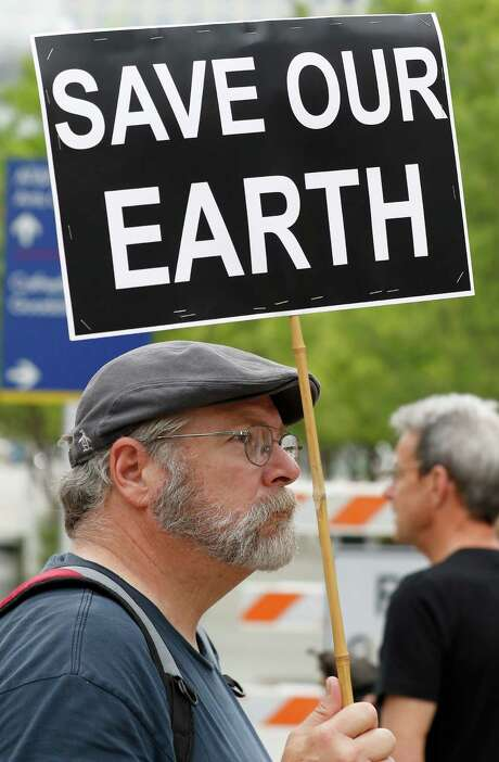 James Strickland protests across from  H. Meyerson Symphony Center where the Exxon Mobil annual shareholder meeting is taking place, in Dallas, Wednesday, May 25, 2016. Shareholders are scheduled to vote Wednesday on resolutions including a policy to limit global warming, put a climate expert on the board, and report on the drilling method known as hydraulic fracturing or fracking. (Jae S. Lee/The Dallas Morning News via AP) Photo: Jae S. Lee, MBR / The Dallas Morning News