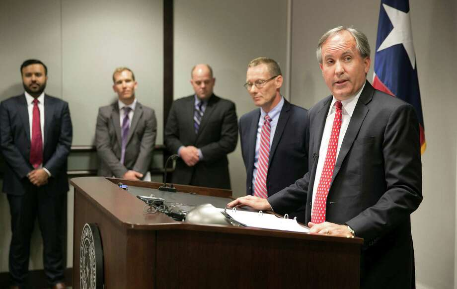 "Texas Attorney General Ken Paxton, right, accuses the federal government of turning schools and workplaces into ""laboratories for a massive social experiment."" Photo: Jay Janner, MBO / Austin American-Statesman"