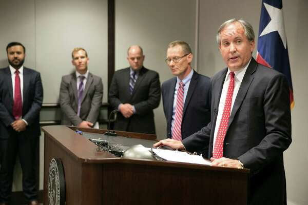 """Texas Attorney General Ken Paxton, right, accuses the federal government of turning schools and workplaces into """"laboratories for a massive social experiment."""""""