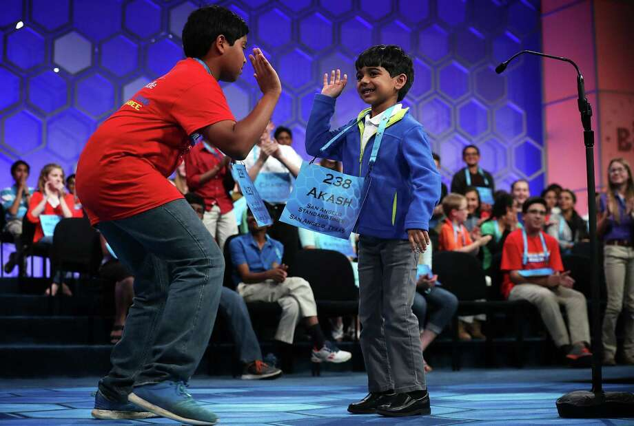 NATIONAL HARBOR, MD - MAY 25:  Six-year-old Akash Vukoti (R) of San Angelo, Texas, hi-fives Alex Iyer (L) of San Antonio, Texas, as he leaves the stage after he misspelled his word in round three of the 2016 Scripps National Spelling Bee May 25, 2016 in National Harbor, Maryland. Students from across the country gathered to competed for top honor of the annual spelling championship.  (Photo by Alex Wong/Getty Images) Photo: Alex Wong, Staff / Getty Images / 2016 Getty Images