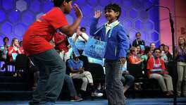 NATIONAL HARBOR, MD - MAY 25:  Six-year-old Akash Vukoti (R) of San Angelo, Texas, hi-fives Alex Iyer (L) of San Antonio, Texas, as he leaves the stage after he misspelled his word in round three of the 2016 Scripps National Spelling Bee May 25, 2016 in National Harbor, Maryland. Students from across the country gathered to competed for top honor of the annual spelling championship.  (Photo by Alex Wong/Getty Images)
