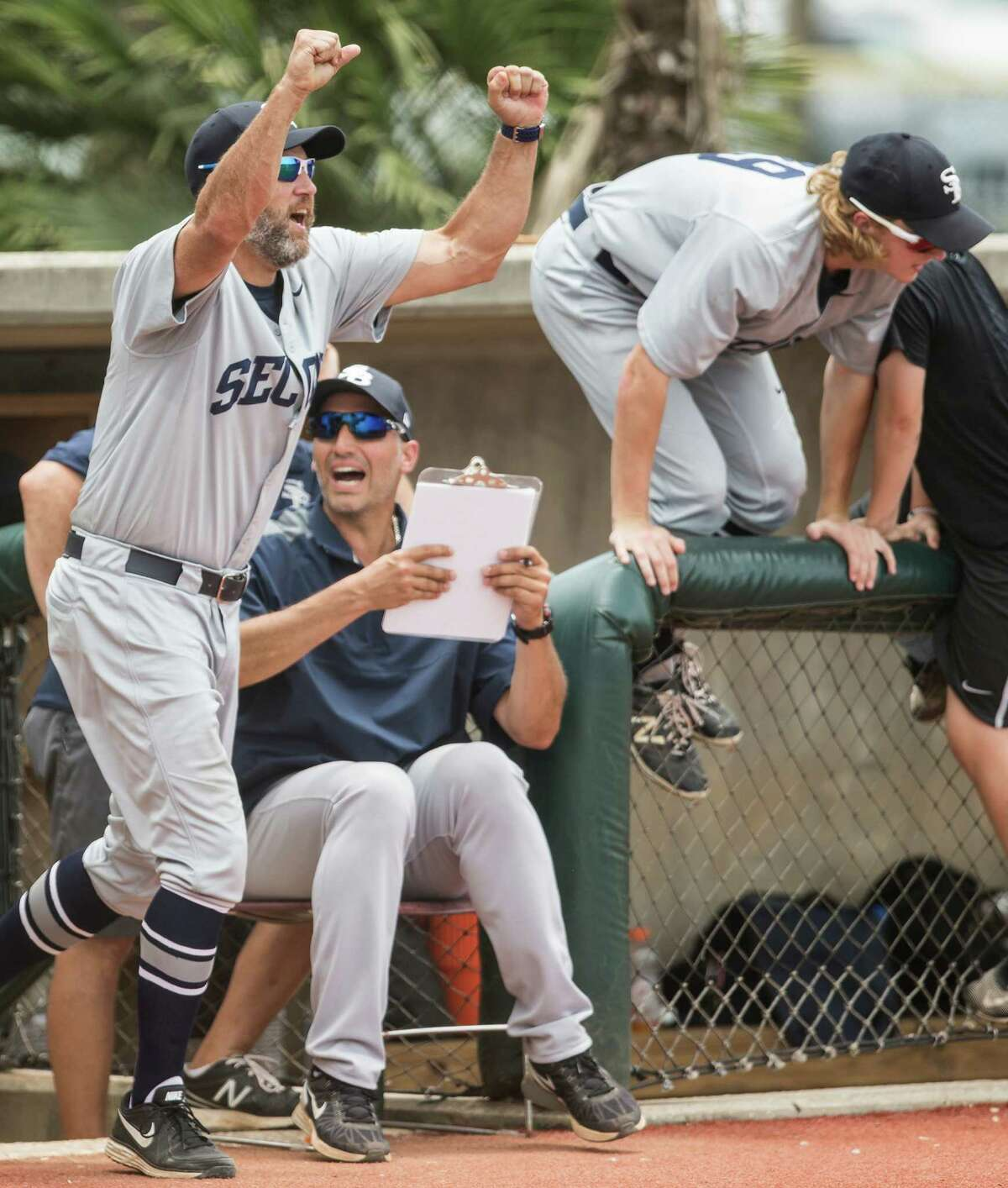 Head coach Lance Berkman, left, and assistant Andy Pettitte, seated, celebrate Second Baptist's 7-2 win over Midland Christian for the TAPPS Class 4A state baseball championship at Baseball USA's Mendel Field on Wednesday.