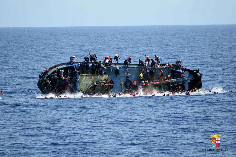People jump out of a boat right before it overturns off the Libyan coast on Wednesday. Amid the continued flows of refugees and migrants to Europe, the German government announced an initiative to boost employment and assimilation with a carrot-and-stick approach. Photo: HOGP / Marina Militare