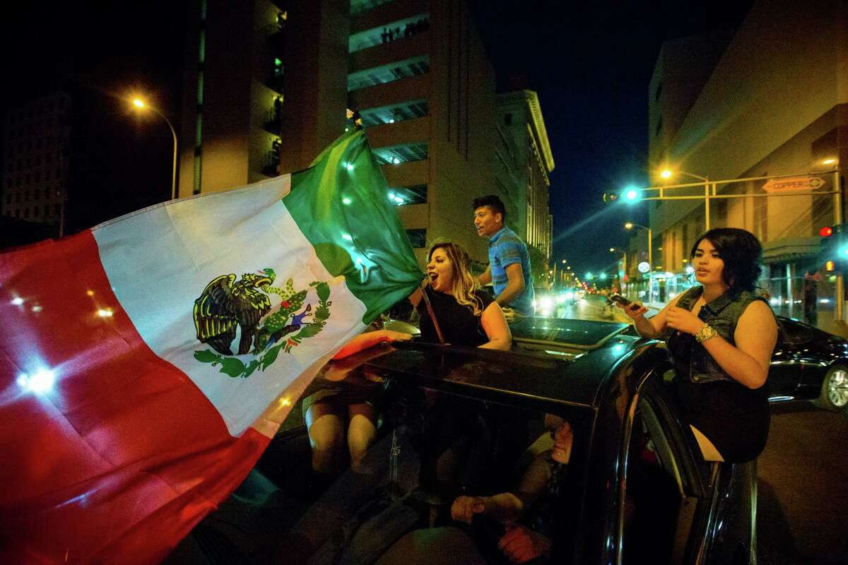 A woman waves the Mexican flag while driving past the Albuquerque Convention Center after a rally by Republican presidential candidate Donald Trump, Tuesday, May 24, 2016, in Albuquerque, N.M. (Jett Loe/The Las Cruces Sun-News via AP) MANDATORY ORG XMIT: NMLCR106