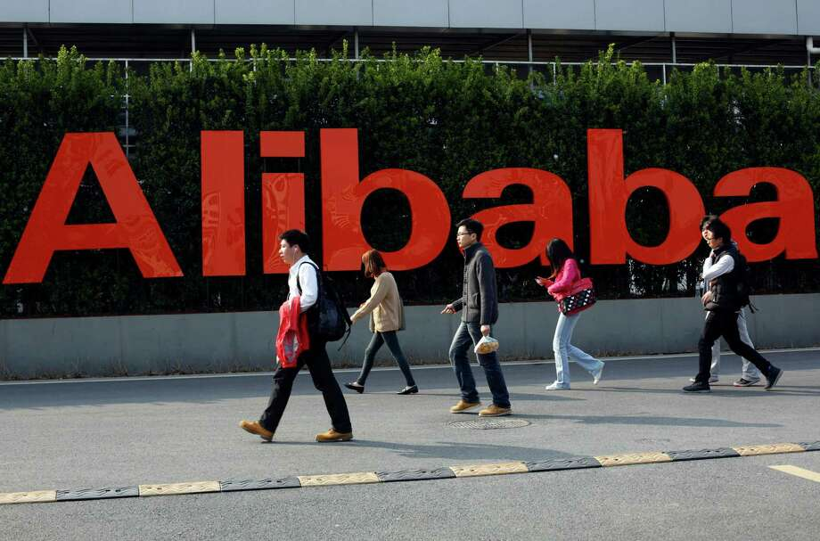 FILE - In this March 17, 2014, file photo, people walk past a company logo at the Alibaba Group headquarters in Hangzhou, in eastern China's Zhejiang province. Chinese e-commerce giant Alibaba is under investigation by U.S. regulators in connection with its accounting practices. Alibaba said in a regulatory filing Tuesday, May 24, 2016, that the U.S. Securities and Exchange Commission has requested documents and information related to its policies and practices for consolidating earnings and for related party transactions, among other things. (Chinatopix via AP, File) CHINA OUT Photo: STR / CHINATOPIX