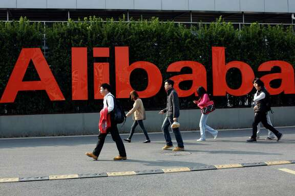 FILE - In this March 17, 2014, file photo, people walk past a company logo at the Alibaba Group headquarters in Hangzhou, in eastern China's Zhejiang province. Chinese e-commerce giant Alibaba is under investigation by U.S. regulators in connection with its accounting practices. Alibaba said in a regulatory filing Tuesday, May 24, 2016, that the U.S. Securities and Exchange Commission has requested documents and information related to its policies and practices for consolidating earnings and for related party transactions, among other things. (Chinatopix via AP, File) CHINA OUT