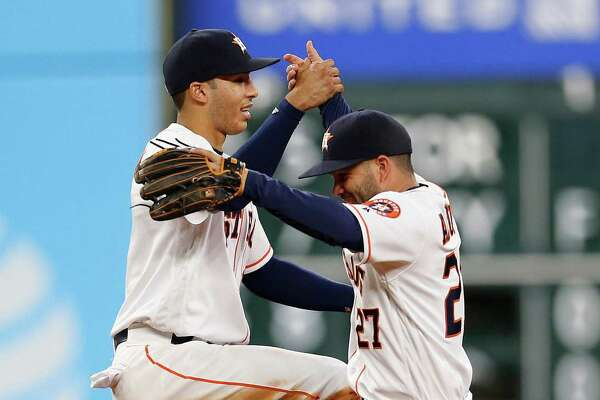 Houston Astros shortstop Carlos Correa (1) and Jose Altuve celebrate the Astros 4-3 win after an MLB baseball game at Minute Maid Park,Wednesday, May 25, 2016.