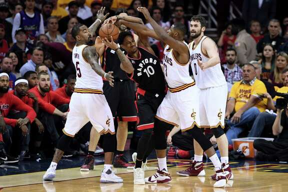 The Cavs' J.R. Smith, left, and Tristan Thompson annoy the Raptors' DeMar DeRozan with their pressure.