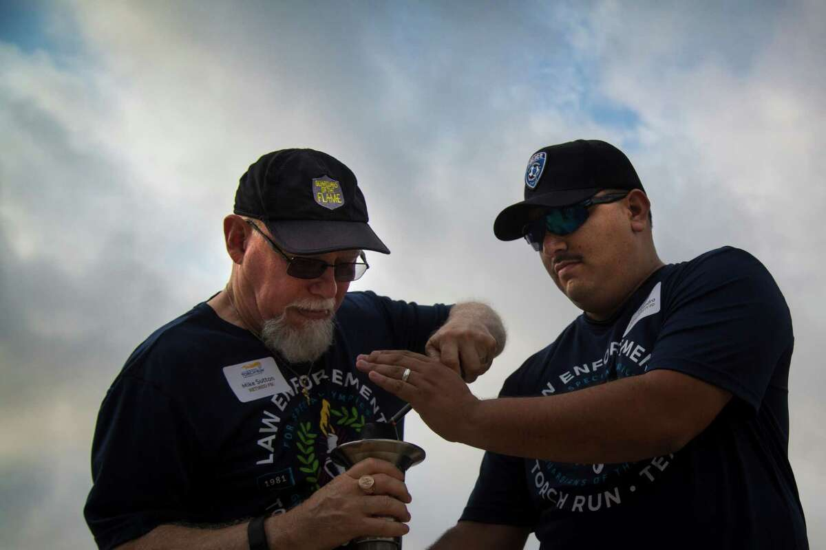 FBI retiree Mike Sutton, left, and Rice University PD Juan Alejandro, right, light the torch that will be carried as part of the Torch Run for Special Olympics at Rice University, Wednesday, May 25, 2016, in Houston.