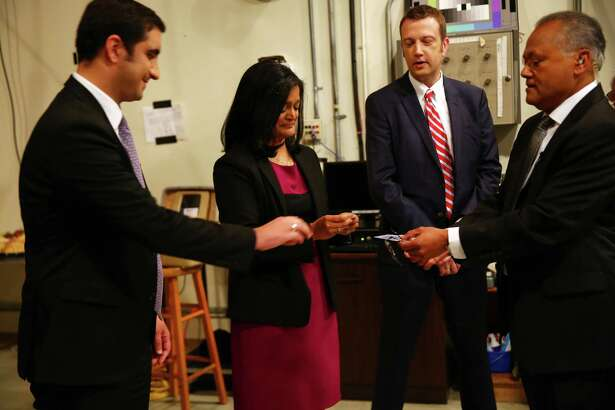 Moderator Enrique Cerna, right, hands out cards to candidates Brady Pi–ero Walkinshaw, left, Pramila Jayapal, and Joe McDermott to determine who will talk first in the 7th Congressional District democratic primary debate, Wednesday, May 25, 2016, the University of Washington.