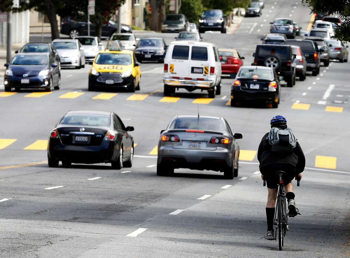 Cars and a bicyclist drive on Masonic Avenue between Fell Street and Geary Boulevard in San Francisco, California, on Wednesday, May 25, 2016.