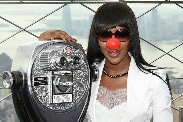 """FILE - In this May 24, 2016 file photo, model Naomi Campbell poses on the observatory of the Empire State Building in honor of Red Nose Day in New York.  With music by Elton John and Blake Shelton, comedy from Tracy Morgan and appearances by more than 60 other celebrities, the live """"Red Nose Day Special"""" on NBC on Thursday, May 26 promises to be as starry a Hollywood awards show, only the winners are children's charities around the world. (Photo by Evan Agostini/Invision/AP)"""