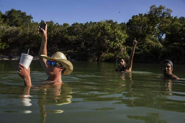 Will Byler (from left), Efrain Lopez and Jesse Requenes wave to a friend driving by on River Road while cooling off near Blanco State Park near the Wayne Smith Dam.