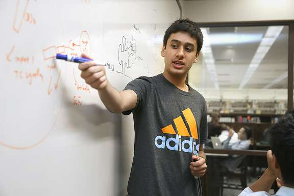Saurav Shroff, 15 years old, talks about a way to localize break down of cancer cells at a meeting of Burlingame Cancer Research (BCR), a group of high school students sharing interests and ideas in the latest cancer research, at the Burlingame library on Wednesday, May 25, 2016 in Burlingame, Calif.