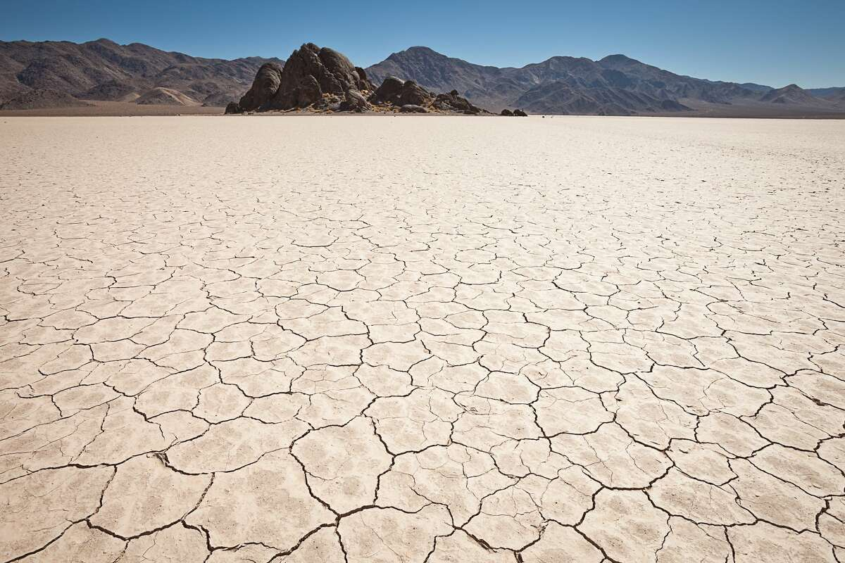 A wide angle view of the cracked mud pattern in the foreground. The Racetrack in Death Valley National Park. A rock outcrop called 'Shiprock' is the dominant feature at one end of the lake.