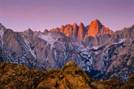 Mount Whitney glows red at sunrise, as seen from the Alabama Hills outside Lone Pine, CA.