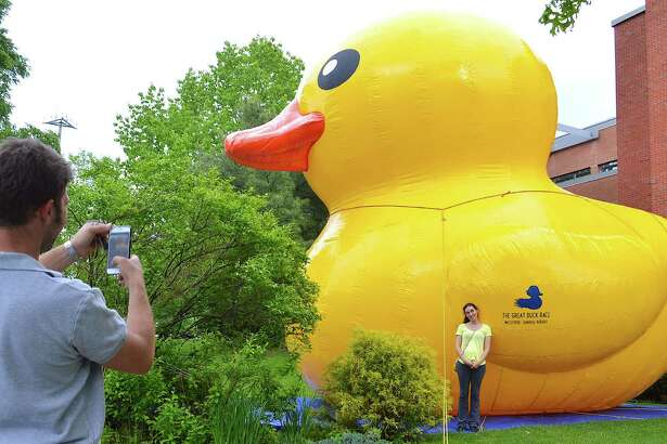 Evan Goldberg photographs Anna Gurevich in front of Sunny, the inflatable duck that is the mascot this year for the Westport Sunrise Rotary Club's Great Duck Race.