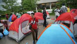 Demonstrators calling for an increase in the minimum wage to $15 per hour pitch tents Wednesday for an overnight protest outside of McDonald's corporate headquarters in Oak Brook, Illinois.