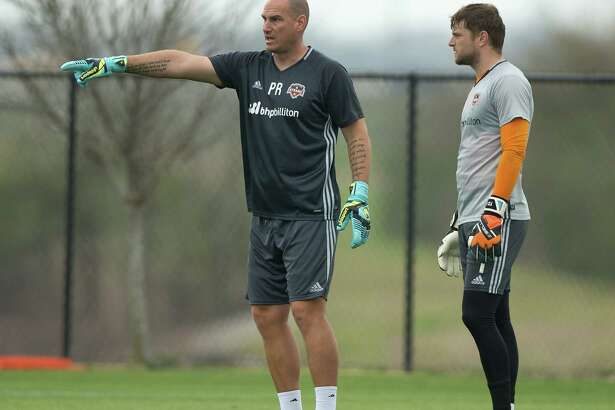 Houston Dynamo goalkeeper Tyler Deric, right, receives some instructions  from Paul Rogers during practice  Tuesday, March 1, 2016.