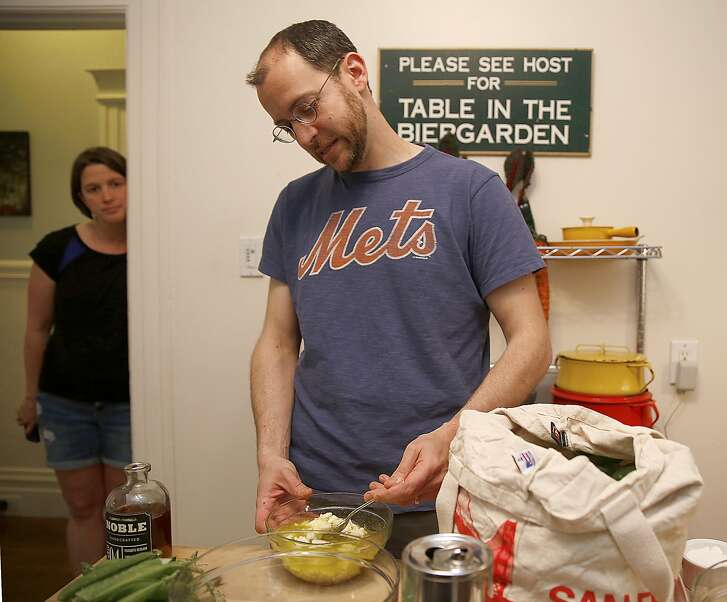 Josh Even (middle) of Tosca mixes olive oil onto a bowl of feta cheese in his kitchen as his wife Katie Even watches him make a pasta dish in San Francisco, Calif., on Monday, May 23, 2016.