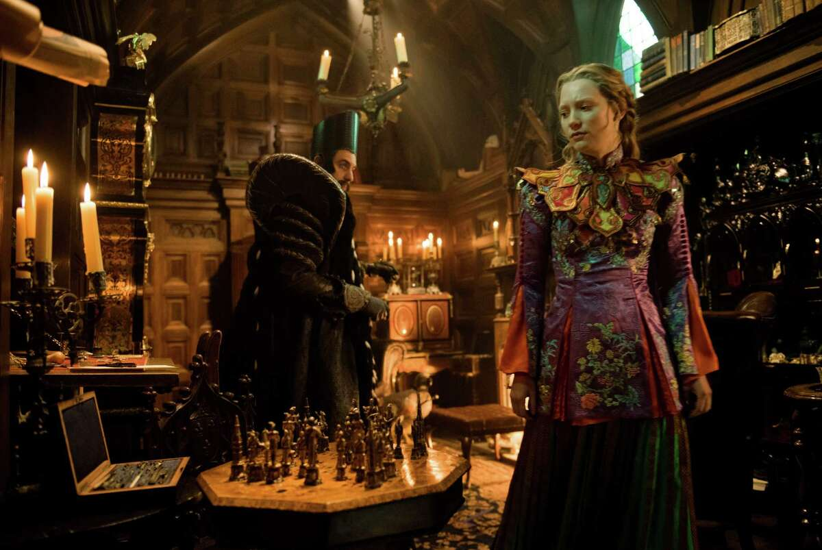 In this image released by Disney, Sacha Baron Cohen, left, and Mia Wasikowska appear in a scene from